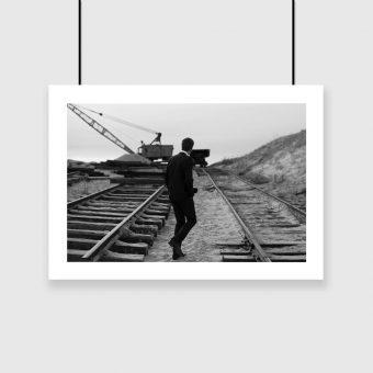 Czarno-biały plakat z mężczyzną między torami